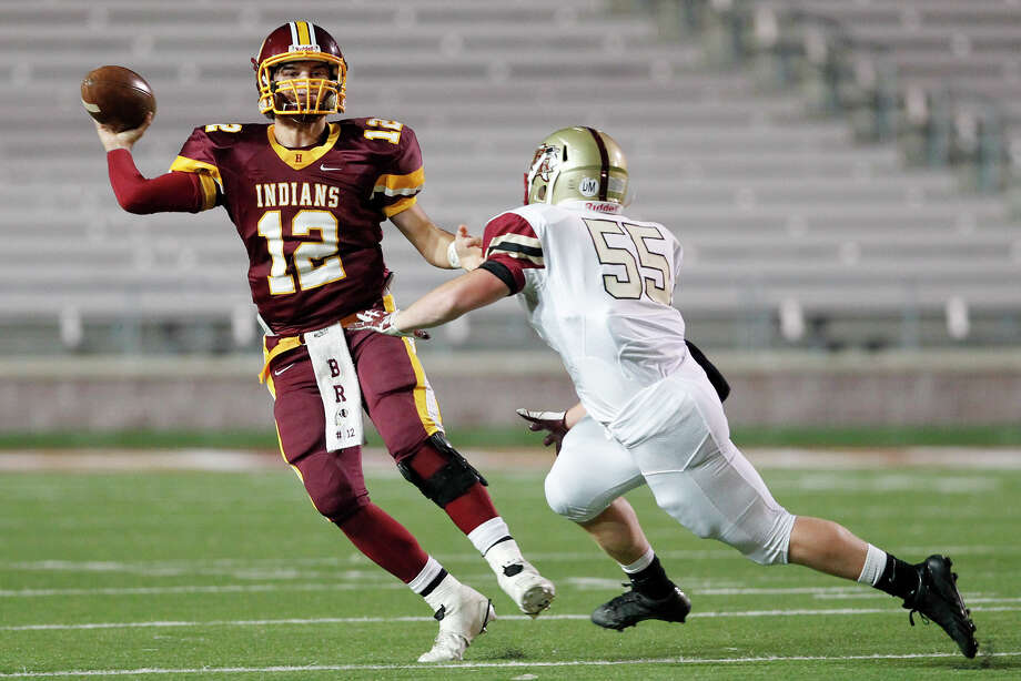 Harlandale's Brandon Ramon looks to pass as Leander Rouse's Ryan Heinrich applies pressure during the first quarter of their Class 4A Division I third round playoff game at Bobcat Stadium in San Marcos on Friday, Nov. 29, 2013. Photo: MARVIN PFEIFFER, Marvin Pfeiffer/ Express-News / Express-News 2013