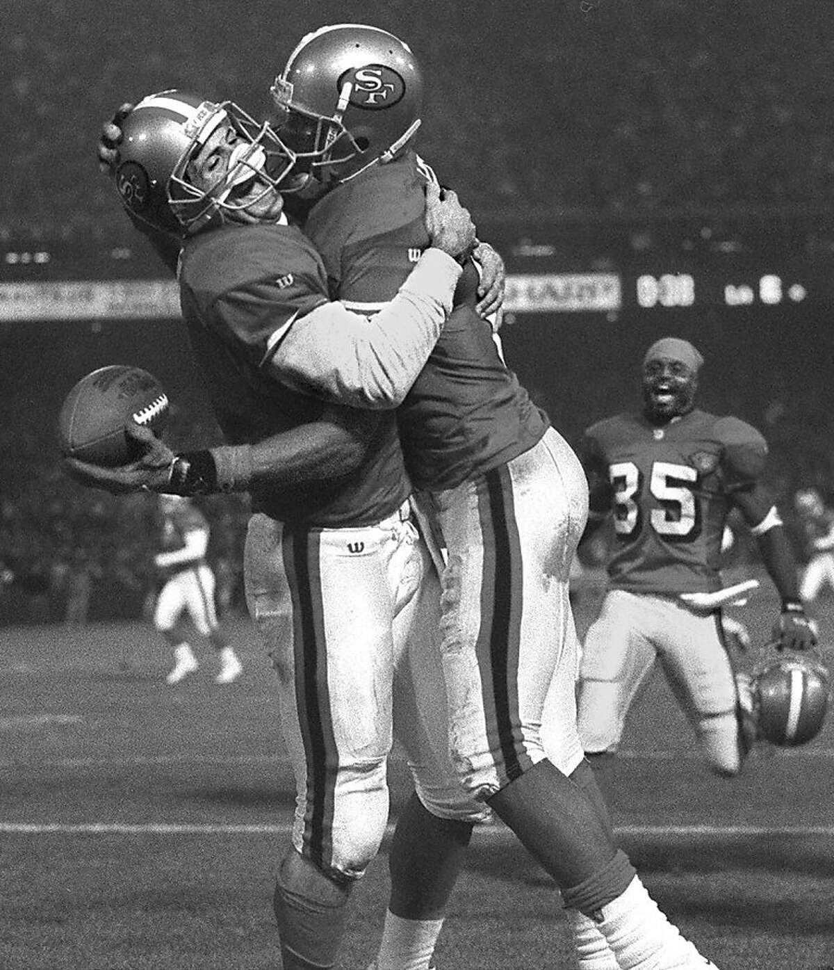 49ERS-RICEYOUNG/C/20NOV94/SP/DF - Steve Young and Jerry Rice embrace after connecting for Rice's 2nd of 3 TDs as the 49ers win over the Ram's at Candlestick Park. Dexter Carter joins in.