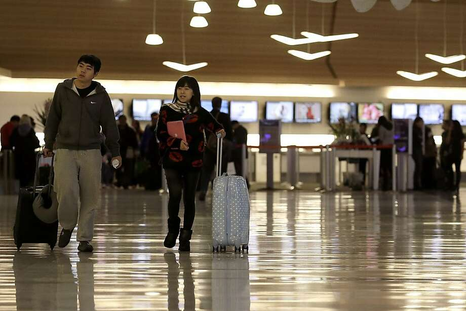 A man and woman walk through the domestic terminal at San Francisco International Airport in San Francisco, Thursday, Nov. 28, 2013. More than 43 million people are to travel over the long holiday weekend, according to AAA. (AP Photo/Jeff Chiu) Photo: Jeff Chiu, Associated Press