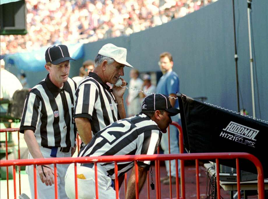 Referee Bob McElwee, center, talks on the phone as he reviews a play with side judge Bill Carollo, left, and head linesman Tony Veteri during an August 1996 preseason game in which the NFL's use of instant replay to get officials' calls correct was just getting started. Photo: BILL KOSTROUN, STR / AP