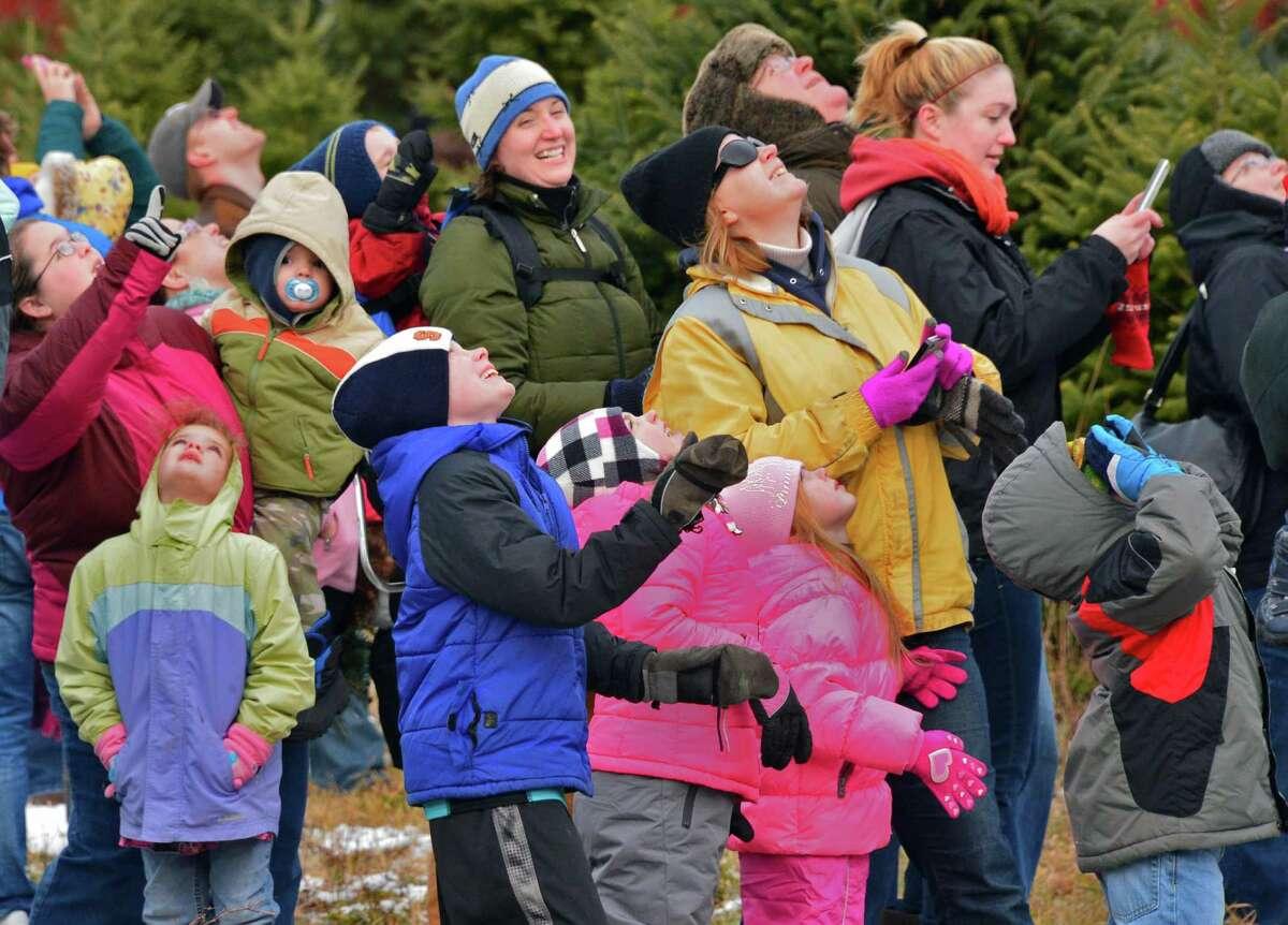 Families watch as Santa parachutes in to the Ellms Christmas Tree Farm Saturday Nov. 30, 2013, in Ballston Spa, NY. (John Carl D'Annibale / Times Union)