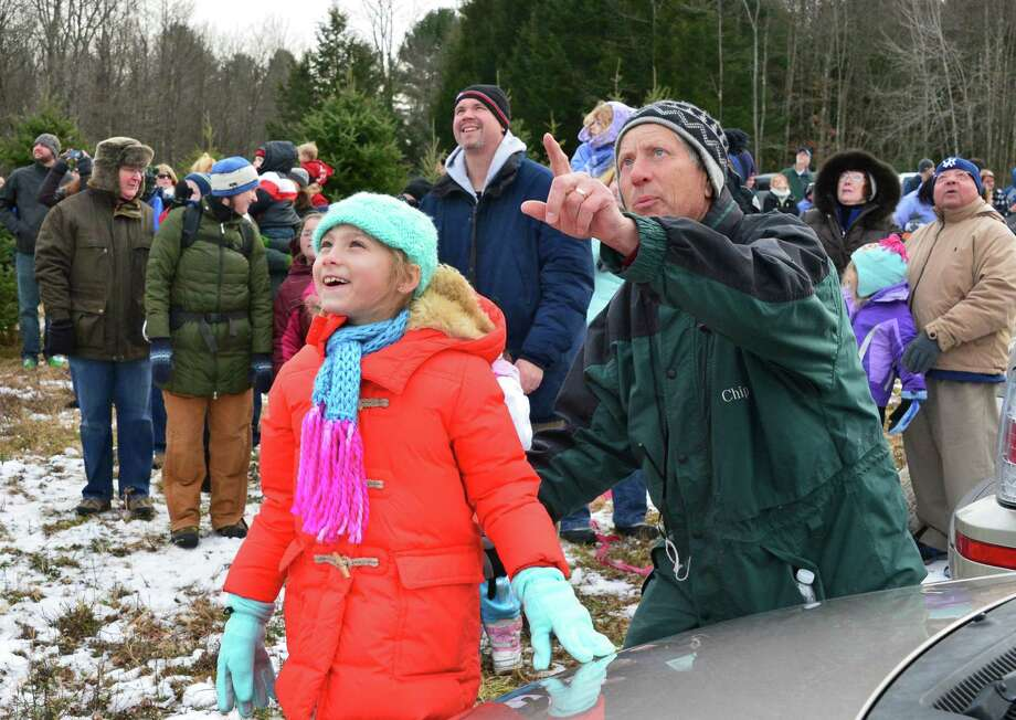 Eight-year-old Calla Presseisen, center, and grandfather Chip Ellms watch as Santa parachutes in to the Ellms  Christmas Tree Farm Saturday Nov. 30, 2013, in Ballston Spa, NY.  (John Carl D'Annibale / Times Union) Photo: John Carl D'Annibale / 00024698A
