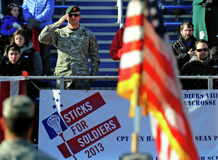 US Army Captain Christopher Couch salutes the flag during the 8th Annual Sticks for Soldiers 2013 Thanksgiving Lacrosse Classic at Fairfield Ludlowe High School's Taft Field in Fairfield, Conn. on Saturday November 30, 2013. Sticks for Soldiers is a non-profit charity lacrosse tournament involving high schools from all over Fairfield County, and which raises money to help wounded troops. One of the event's honorees is US Army Captain Benjamin Harrow, seated at right.Also honored was US Army Specialist Sean Pesce, who is seated at left. Photo: Christian Abraham / Connecticut Post
