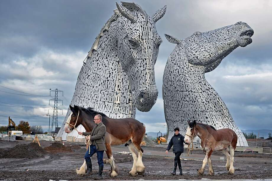 Andy Scott stands with Clydesdale Horses Duke and Baron and Donna Auchinvole during a topping out ceremony at The Kelpies on November 27, 2013 in Falkirk, Scotland. Construction work has been completed on Andy Scott's Kelpies, the world's largest pair of equine sculptures and one of the UKs tallest pieces of public art. The 30 metre tall Kelpies have cost £5million to complete and play a central role in the £43 million, 350-hectare Helix land transformational project between Falkirk and Grangemouth. Photo: Jeff J Mitchell, Getty Images