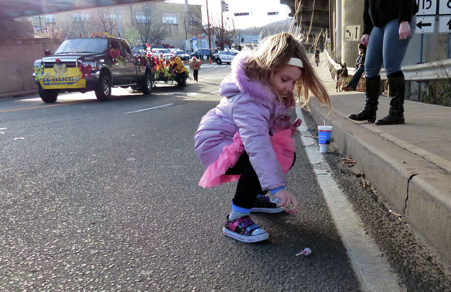 Brooke Rodgerson, 4, of Naugatuck, rushes out to grab some candy thrown out onto the street, during the 42nd Annual Seymour Merchants Christmas Parade in downtown Seymour, Conn. on Saturday November 30, 2013. Photo: Christian Abraham / Connecticut Post