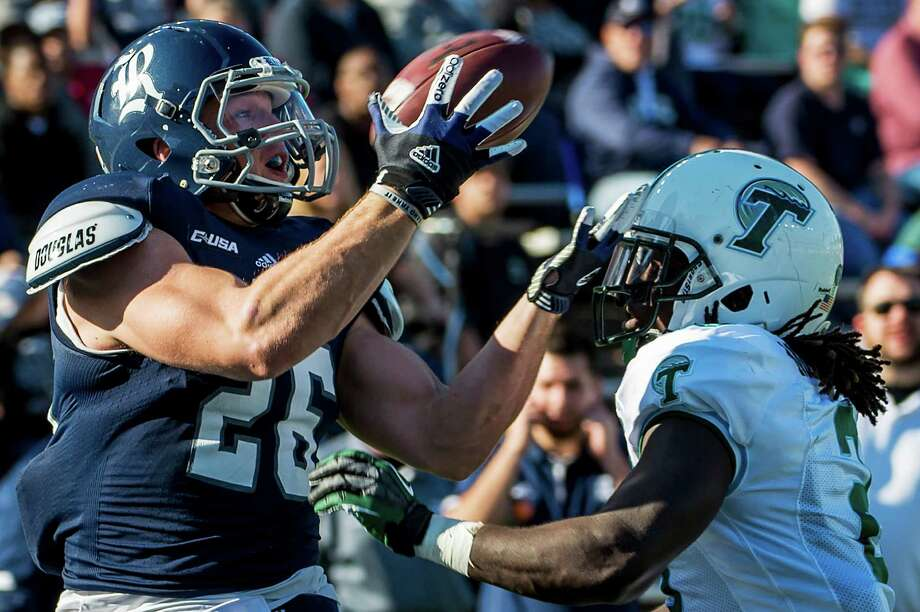 Rice running back Turner Petersen (26) catches a 19-yard touchdown pass as Tulane safety Darion Monroe (2) defends during the first quarter of a college football game at Rice Stadium, Saturday, Nov. 30, 2013, in Houston. Photo: Smiley N. Pool, Houston Chronicle / © 2013  Houston Chronicle