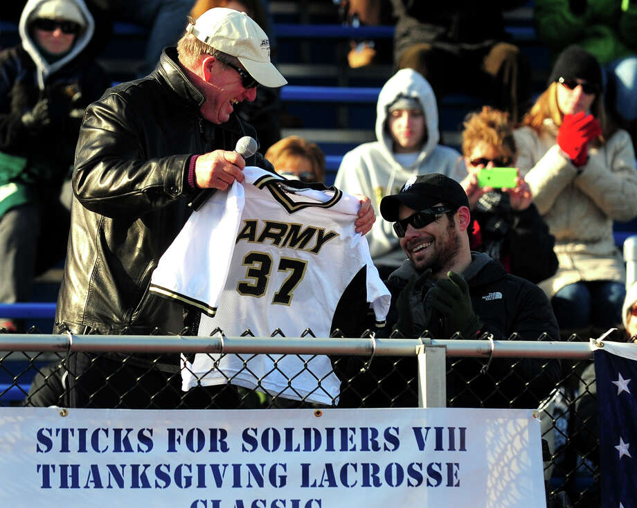 US Army Lacrosse Coach Jack Emmer presents US Army Captain Benjamin Harrow with his old Army jersey, during the 8th Annual Sticks for Soldiers 2013 Thanksgiving Lacrosse Classic at Fairfield Ludlowe High School's Taft Field in Fairfield, Conn. on Saturday November 30, 2013. Sticks for Soldiers is a non-profit charity lacrosse tournament involving high schools from all over Fairfield County, and which raises money to help wounded troops. The event honored Captain Harrow and US Army Specialist Sean Pesce. Photo: Christian Abraham / Connecticut Post