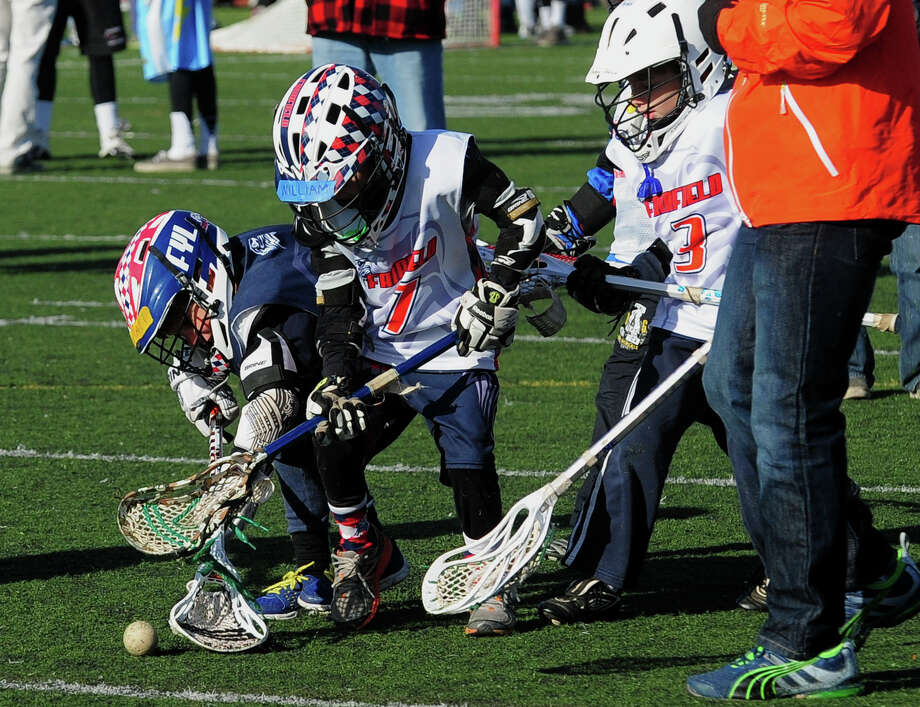Seven and eight year old kids from the Fairfield Youth Lacrosse team play a match during the 8th Annual Sticks for Soldiers 2013 Thanksgiving Lacrosse Classic at Fairfield Ludlowe High School's Taft Field in Fairfield, Conn. on Saturday November 30, 2013. Sticks for Soldiers is a non-profit charity lacrosse tournament involving high schools from all over Fairfield County, and which raises money to help wounded troops. The event's honorees this year are US Army Captain Benjamin Harrow and US Army Specialist Sean Pesce. Photo: Christian Abraham / Connecticut Post