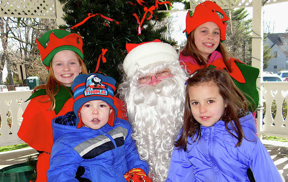 Liam and Abby McCoy, ages 3 and 5, of Fairfield, visit with Santa while elves Isabelle Morse and Elizabeth Sargeant look on during the annual arrival ceremonies for Santa organized by the Fairfield Chamber of Commerce. Photo: Mike Lauterborn / Fairfield Citizen contributed