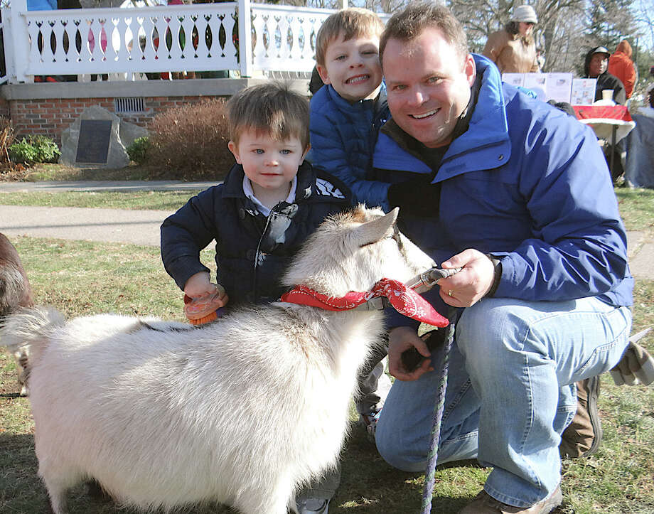 Fairfield Representative Town Meeting member Chris Tymniak and sons James, 1, and Sam, 5, get to know a goat at the peeting zoo on Sherman Green during Saturday's arrival ceremonies for Santa. Photo: Mike Lauterborn / Fairfield Citizen contributed
