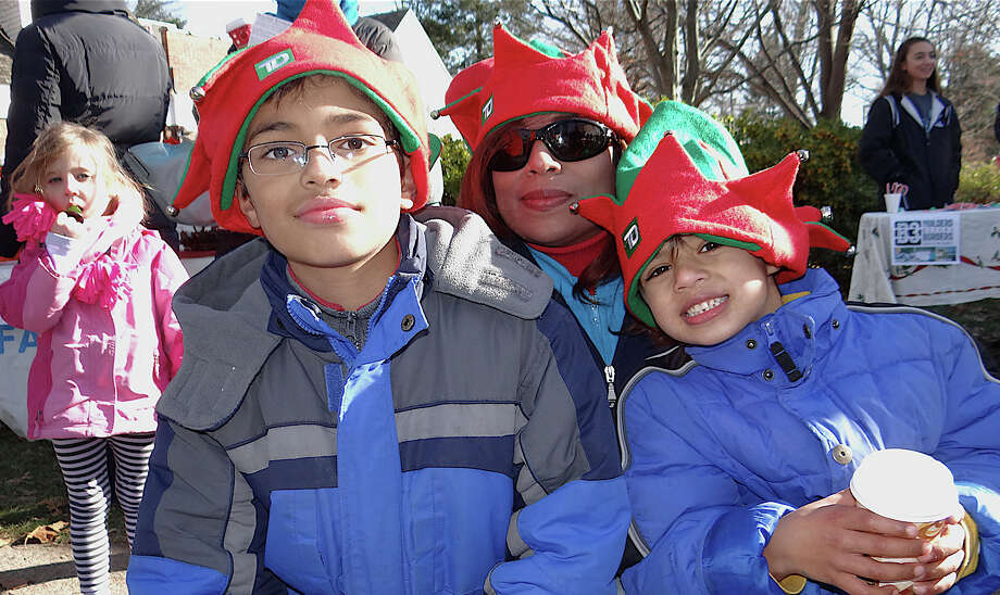 Mala Payman Buckley and sons Thomas, 9, and Matthew, 5, wait in line to meet Santa on Saturday at Sherman Green. Photo: Mike Lauterborn / Fairfield Citizen contributed