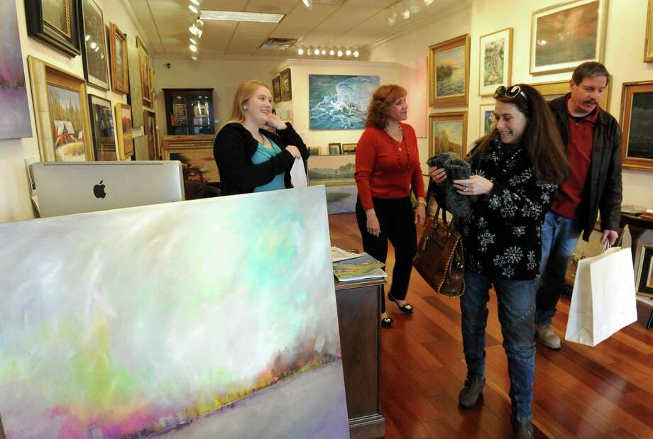 Asher Weiner, right, and his wife Nirit Weiner of Voorheesville purchase art from the Sorelle Gallery, owned by Sandra Pelletier, center. Gallery assistant director Heather Pominville is at left. It was during Small Business Saturday at Stuyvesant Plaza on Saturday Nov. 30, 2013 in Albany, N.Y. (Michael P. Farrell/Times Union) Photo: Michael P. Farrell / 00024847A