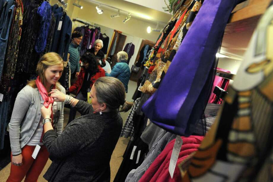 Silver Parrot manager Christie Waldman, center, ties a scarf on Melissa Miller of Latham during small business Saturday at Stuyvesant Plaza on Saturday Nov. 30, 2013 in Albany, N.Y. (Michael P. Farrell/Times Union) Photo: Michael P. Farrell / 00024847A