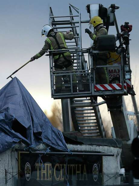 Rescue workers shift through the wreckage Saturday following the helicopter crash at the Clutha Bar in Glasgow.  The pub was packed Friday night when a chopper fell through the roof. Photo: Scott Heppell / Associated Press