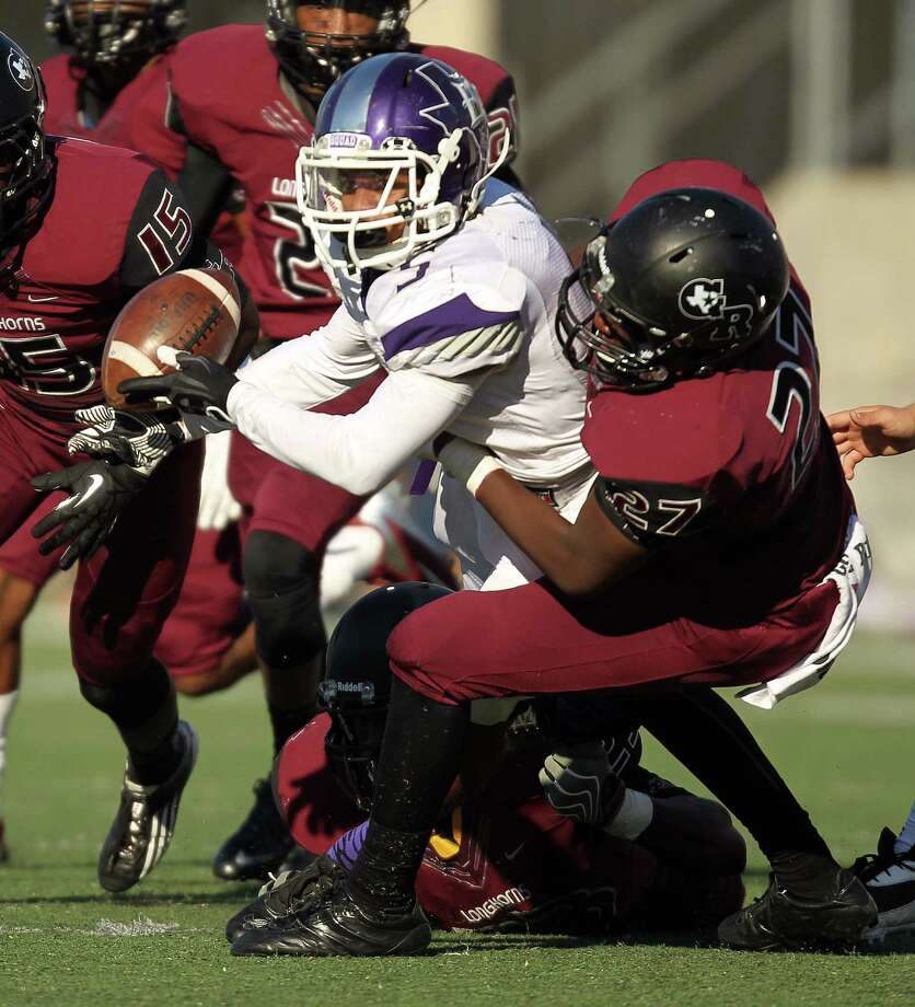 Elgin's Da'Trean Simmons, center, fumbles the ball after being tackled by George Ranch's Quincy Wande during the second half of a high school football playoff game, Saturday, November 30, 2013, at the Berry Center in Cypress. Photo: Eric Christian Smith, For The Chronicle