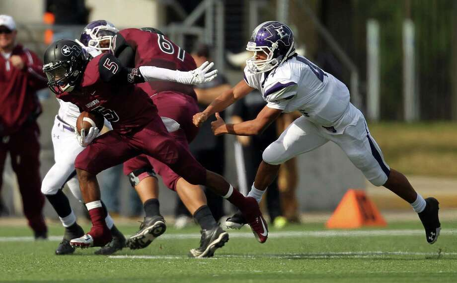 George Ranch's Xavian Marks (5) breaks the tackle of Elgin's Jordan Smith during the first half of a high school football playoff game, Saturday, November 30, 2013, at the Berry Center in Cypress. Photo: Eric Christian Smith, For The Chronicle