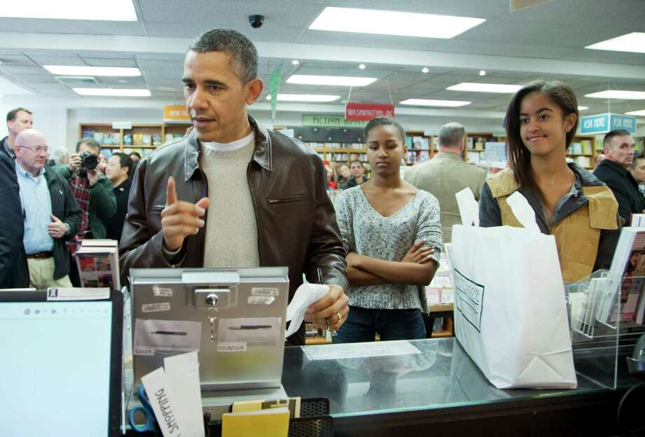 President Barack Obama, with daughters Sasha, center, and Malia, pays for his purchase the the local bookstore Politics and Prose in northwest Washington, Saturday, Nov. 30, 2013.  (AP Photo/Manuel Balce Ceneta) ORG XMIT: WHMC104 Photo: Manuel Balce Ceneta / AP