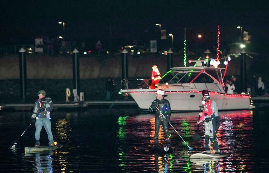 Left to right; Coming into the docks next to the Crab Shell restaurant, Jack Eagen, Michael Pensiero, and Michael Barnaba participating in the annual Thanksgiving weekend Stamford Harbor Parade of Lights on their paddle boards. Stamford, CT. Saturday, November, 30th, 2013. Photo: Mark Conrad / Connecticut Post Freelance