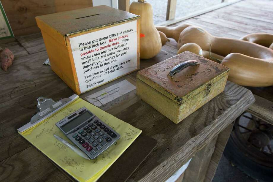 The honor-system cash box at Dennis and Darlene Hess' farm stand in Litiz, Pa., shows that there are still trusters around despite a poll conducted last month that showed Americans are increasingly suspicious of each other in everyday encounters. Photo: Matt Rourke / Associated Press