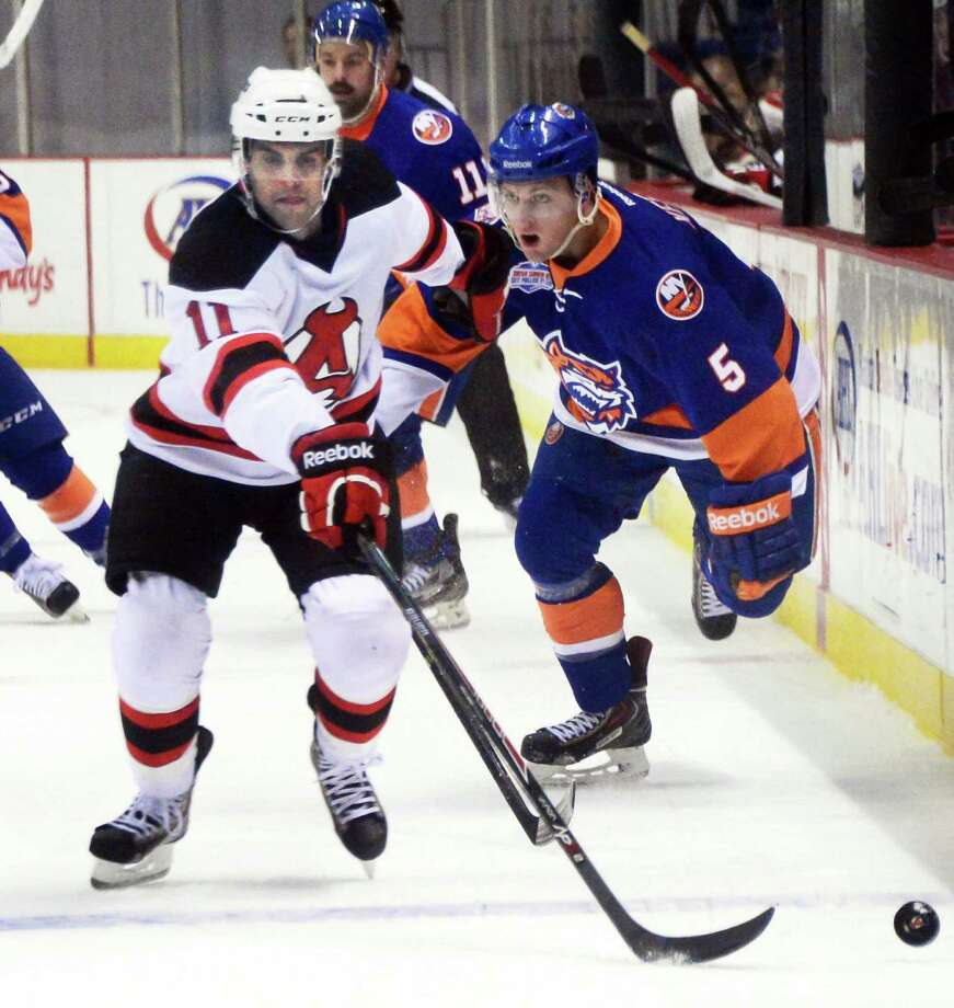 Albany Devils' #11 Kelly Zajac, left, and Bridgeport Sound Tigers' #5 Mike Keenan during Saturday's game at the Times Union Center Nov. 30, 2013, in Albany, NY.  (John Carl D'Annibale / Times Union) Photo: John Carl D'Annibale / 00024825A