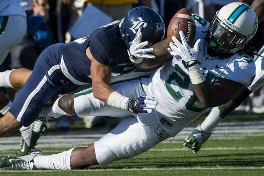 Tulane running back Rob Kelley fumbles as he is hit by Rice cornerback Bryce Callahan. Photo: Smiley N. Pool, Houston Chronicle