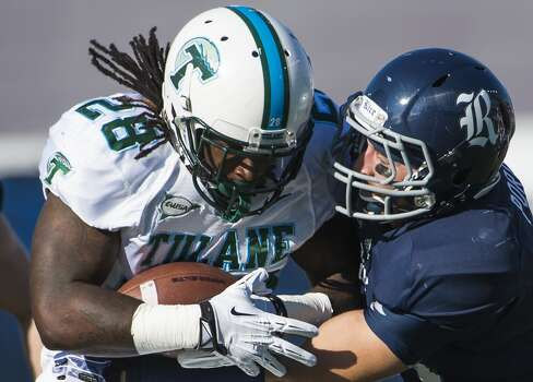 Tulane running back Rob Kelley is stopped for a loss by Rice safety Paul Porras. Photo: Smiley N. Pool, Houston Chronicle