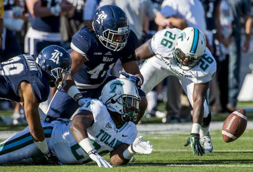 Tulane running back Rob Kelley watches his fumble bounce away after a hit from Rice cornerback Bryce Callahan. Photo: Smiley N. Pool, Houston Chronicle