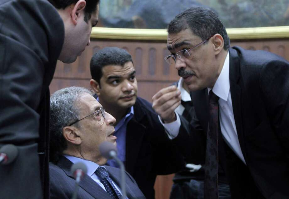 Amr Moussa (second from left), the chairman of the panel tasked with amending Egypt's Islamist-drafted constitution, listens to Diaa Rashwan (right) before they begin to vote. Photo: Amr Nabil / Associated Press
