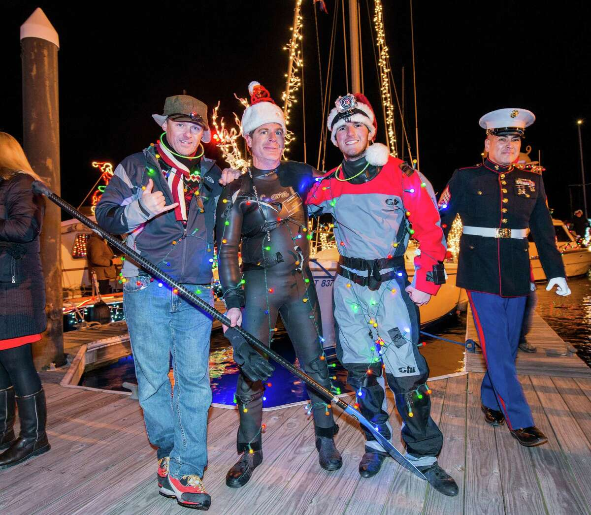 Left to right; Jack Eagen, Michael Pensiero, and Michael Barnaba pose for a photo on the docks next to the Crab Shell restaurant, Stamford, CT. The three participated in the annual Thanksgiving weekend Stamford Harbor Parade of Lights on their paddle boards.