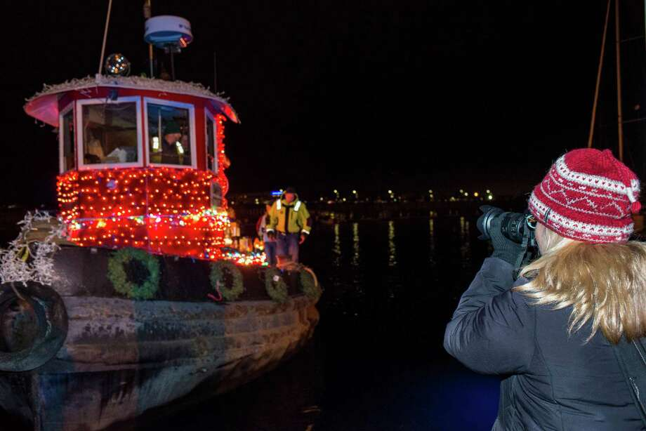 Sharon Benton, one of the judges in the annual Thanksgiving weekend Stamford Harbor Parade of Lights event photographs one of the boats coming into the docks next to the Crab Shell restaurant, Stamford, CT on Saturday, November, 30th, 2013. Photo: Mark Conrad / Connecticut Post Freelance