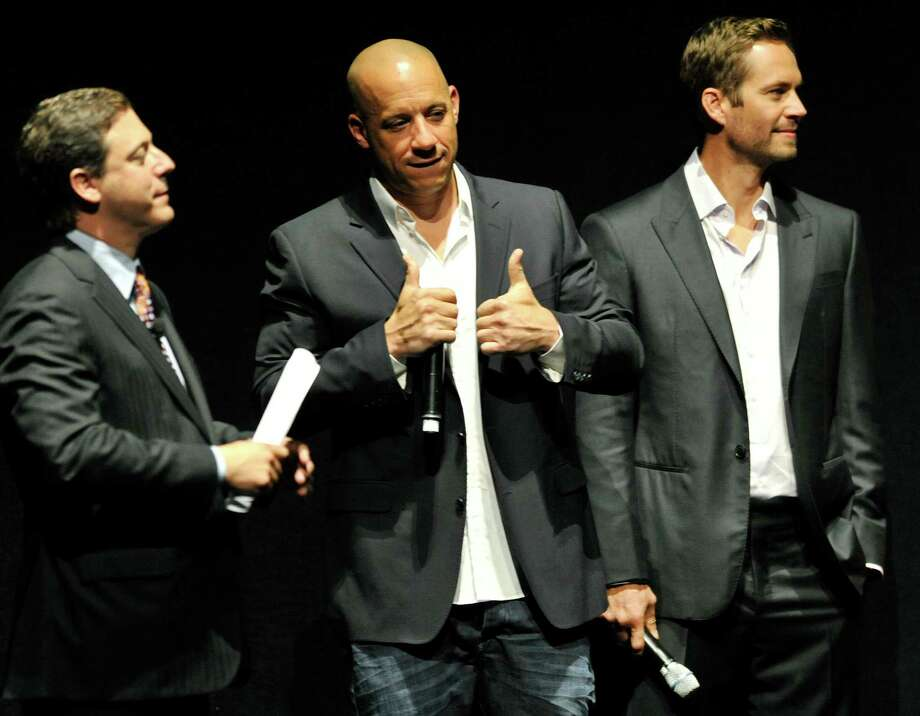 "Vin Diesel, center, a cast member in the forthcoming film ""Fast & Furious 6,"" flashes a thumbs-up sign for the audience as Universal Pictures Chairman Adam Fogelson, left, and fellow cast member Paul Walker watch during CinemaCon 2013 at Caesars Palace on Tuesday, April 16, 2013 in Las Vegas. (Photo by Chris Pizzello/Invision/AP) Photo: Chris Pizzello, Associated Press / Invision"