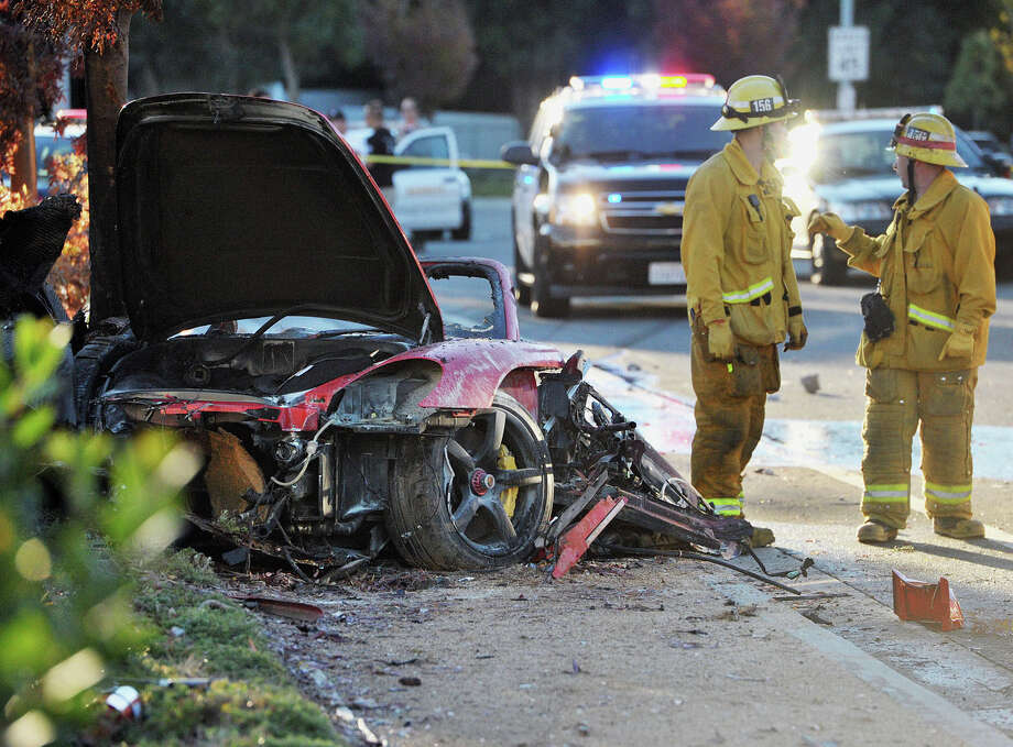 "First responders gather evidence near the wreckage of a Porsche sports car that crashed into a light pole on Hercules Street near Kelly Johnson Parkway in Valencia on Saturday, Nov. 30, 2013. A publicist for actor Paul Walker says the star of the ""Fast & Furious"" movie series has died in a car crash north of Los Angeles. He was 40. Ame Van Iden says Walker died Saturday afternoon. No further details were released. (AP Photo/The Santa Clarita Valley Signal, Dan Watson) Photo: Dan Watson, Associated Press / The Santa Clarita Valley Signal"