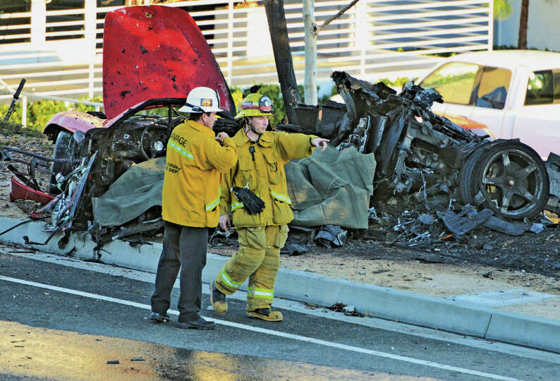 First responders gather evidence near the wreckage of a Porsche sports car that crashed into a light