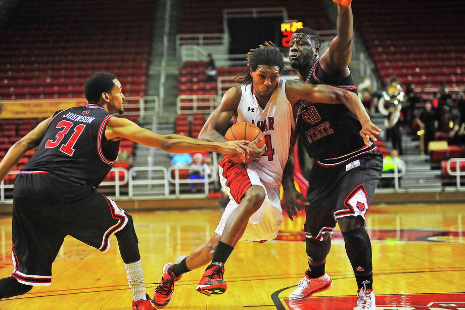 Lamar University Cardinals Amos Wilson drives the ball past Arkansas State Melvin Johnson III, during the second period at the Montagne Center, Saturday. The Cardinals lost with the final score of 89-95. Michael Rivera/@michaelrivera88