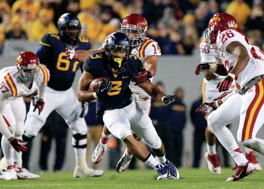 West Virginia's Charles Sims looks for running room against Iowa State during the Mountaineers' 52-44 triple-overtime loss to the Cyclones. Sims, a transfer from the University of Houston, rushed for 149 yards Saturday and finished his one season with West Virginia with 1,095 yards. Photo: Chris Jackson, FRE / FR170573