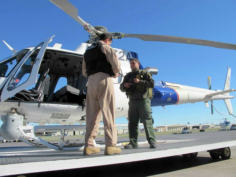 Jacob Dreher (left), a U.S. Customs and Border Protection agent, and EMT-trained Border Patrol agent Mentor Cavazos demonstrate preparations for an air patrol at an agency office in McAllen. Photo: Christopher Sherman / Associated Press