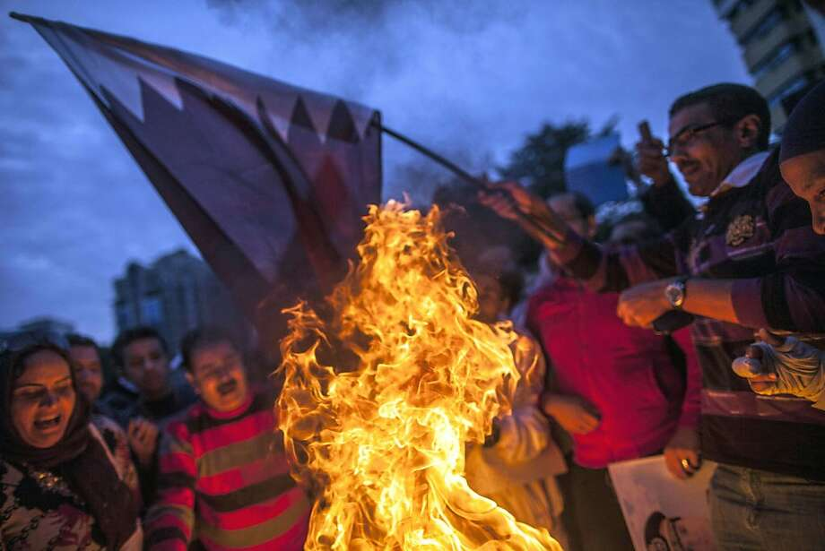 TOPSHOTS Supporters of Egypt's military chief Abdel Fattah al-Sisi burn a Qatari national flag during a demonstration outside the Qatari embassy in Cairo on November 30, 2013. TOPSHOTS/AFP PHOTO/MAHMOUD KHALEDMAHMOUD KHALED/AFP/Getty Images Photo: Mahmoud Khaled, AFP/Getty Images