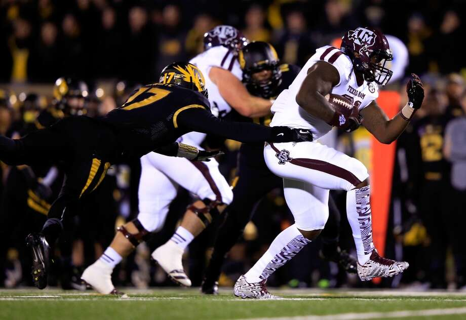 Running back Tra Carson #21 of the Aggies carries the ball for a touchdown as safety Matt White #17 of the Tigers defends. Photo: Jamie Squire, Getty Images