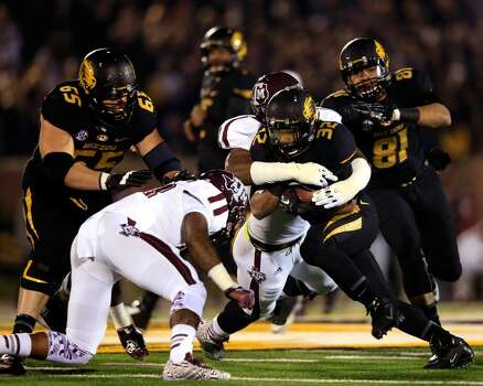 Running back Russell Hansbrough #32 of the Tigers carries the ball. Photo: Jamie Squire, Getty Images