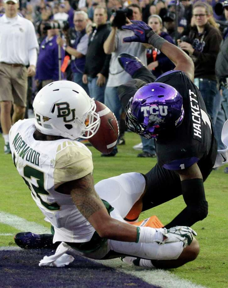 Baylor's Levi Norwood, left, tumbles past TCU's Chris Hackett on a 33-yard touchdown reception that turned out to be the winning margin. Photo: LM Otero, STF / AP