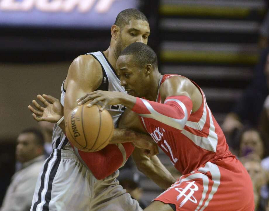 Tim Duncan of the San Antonio Spurs, left, battles Houston Rockets center Dwight Howard during first-half NBA action at the AT&T Center on Saturday, Nov. 30, 2013. Photo: Billy Calzada, San Antonio Express-News