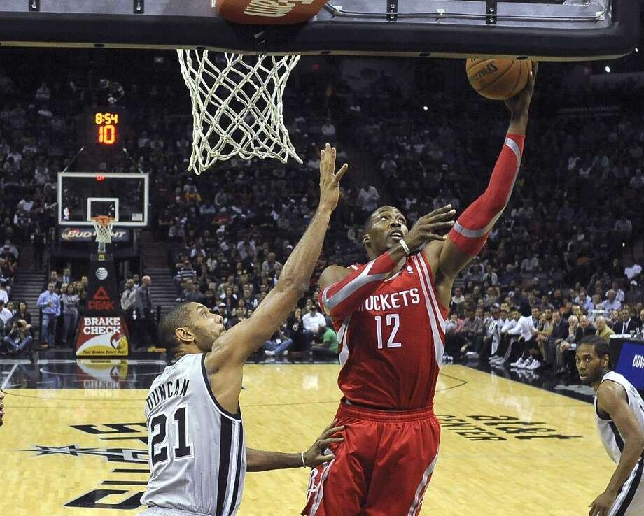 Tim Duncan of the San Antonio Spurs defends as Dwight Howard of the Houston Rockets shoots during NBA action at the AT&T Center on Saturday, Nov. 30, 2013. Photo: Billy Calzada, San Antonio Express-News