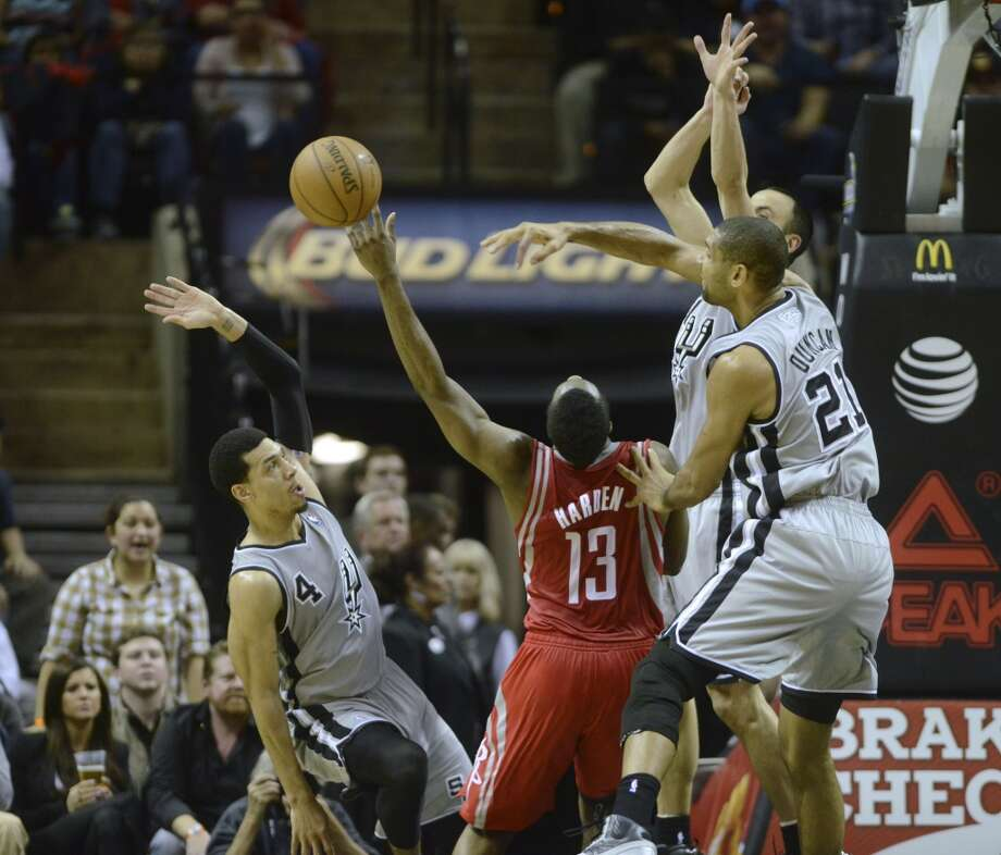 James Harden of the Houston Rockets is stopped by San Antonio defenders Danny Green (4), Manu Ginobili and Tim Duncan (21) during second-half NBA action at the AT&T Center on Saturday, Nov. 30, 2013. Photo: Billy Calzada, San Antonio Express-News