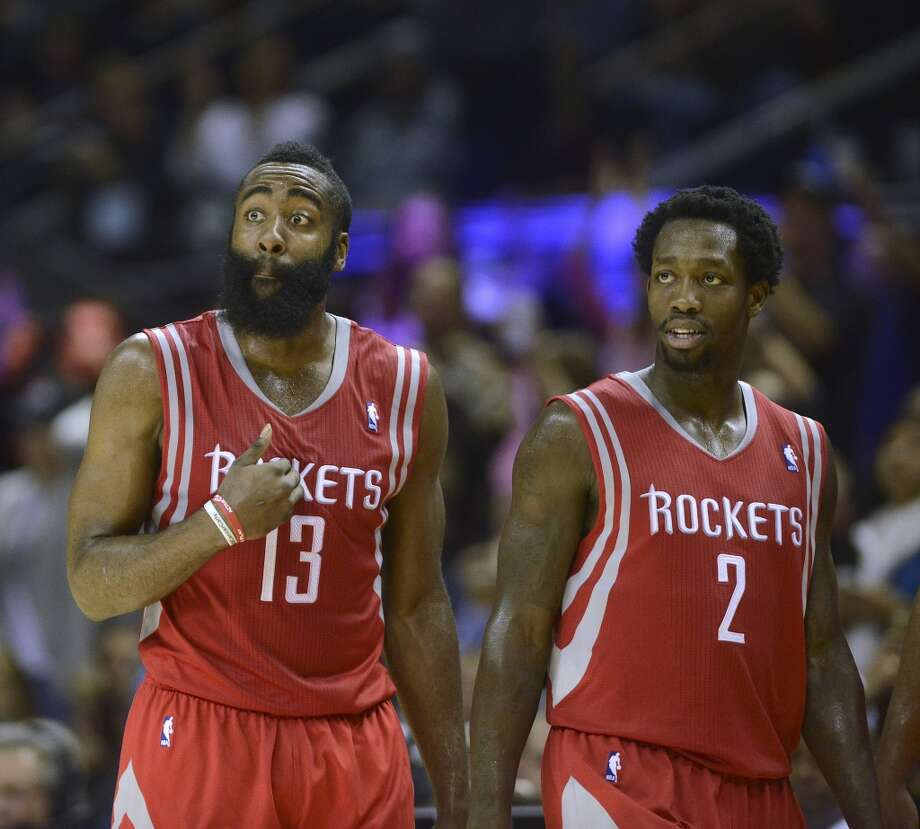 James Harden of the Houston Rockets (13) reacts as he walks with teammate Patrick Beverley during a timeout as they go on to defeat the San Antonio Spurs, 112-106, at the AT&T Center on Saturday, Nov. 30, 2013. Photo: Billy Calzada, San Antonio Express-News