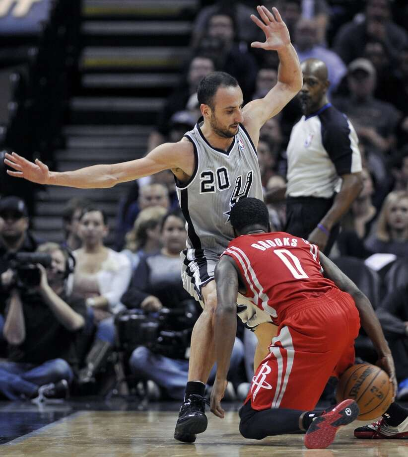 San Antonio Spurs shooting guard Manu Ginobili (20), of Argentina, collides with Houston Rockets point guard Aaron Brooks during the first half of an NBA basketball game Saturday, Nov. 30, 2013, in San Antonio. Photo: Darren Abate, Associated Press
