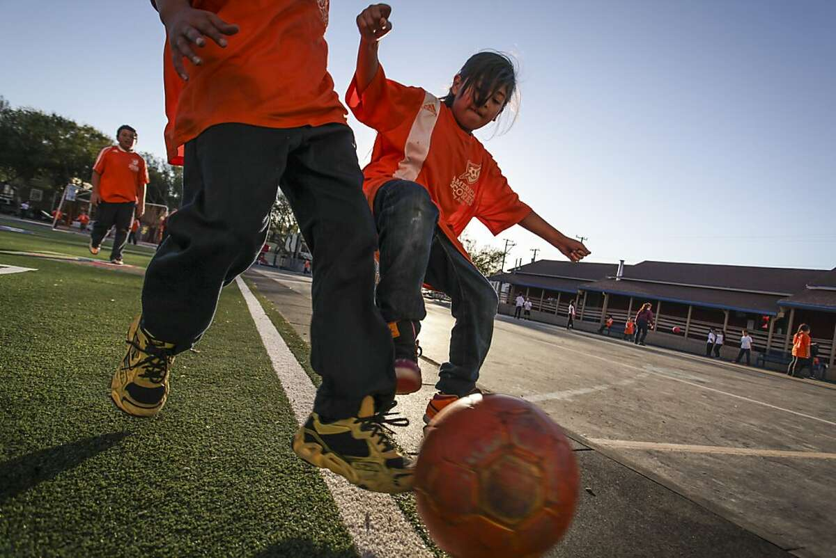 Children play soccer during a free after-school program on a new turf field installed by America Scores Bay Area, a nonprofit that helps to turn concrete playgrounds at low-income schools into playing fields, at Cleveland Elementary in San Francisco on November 22nd 2013.