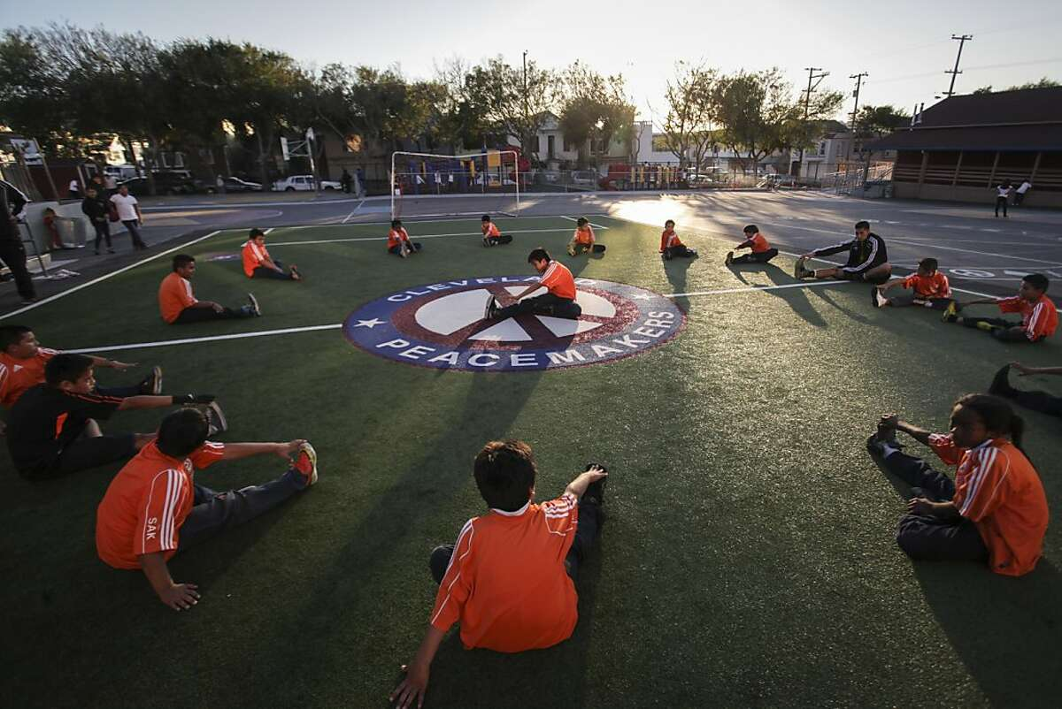 Children stretch before playing a game of soccer during a free after-school program on a new turf field installed by America Scores Bay Area, a nonprofit that helps to turn concrete playgrounds at low-income schools into playing fields, at Cleveland Elementary in San Francisco on November 22nd 2013.
