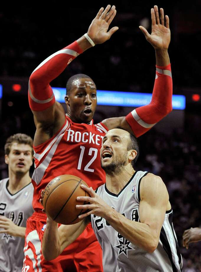 The Rockets' Dwight Howard looms over the Spurs'  Manu Ginobili as he goes up for a shot in the first half. Photo: Darren Abate, FRE / FR115 AP
