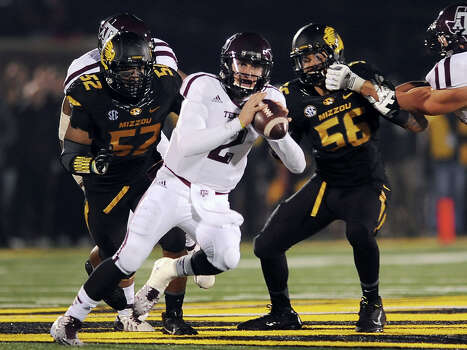 Johnny Manziel considers his options as Missouri defensive linemen Michael Sam, left, and Shane Ray try to catch up to the A&M quarterback during the second quarter Saturday night. Photo: L.G. Patterson, FRE / FR23535 AP