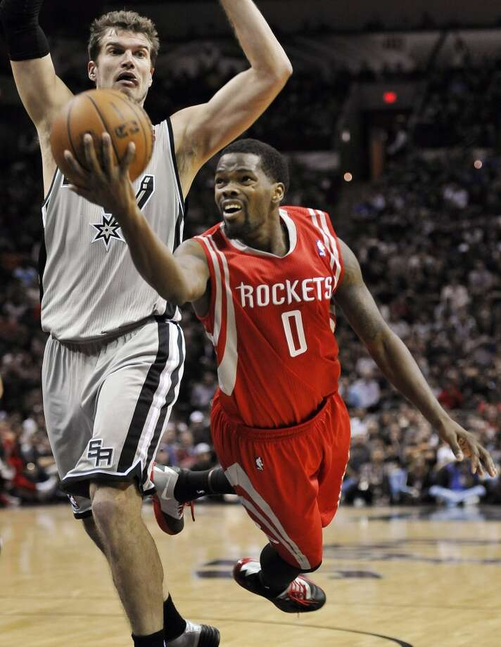 Rockets point guard Aaron Brooks, right, shoots against Spurs power forward Tiago Splitter. Photo: Darren Abate, Associated Press
